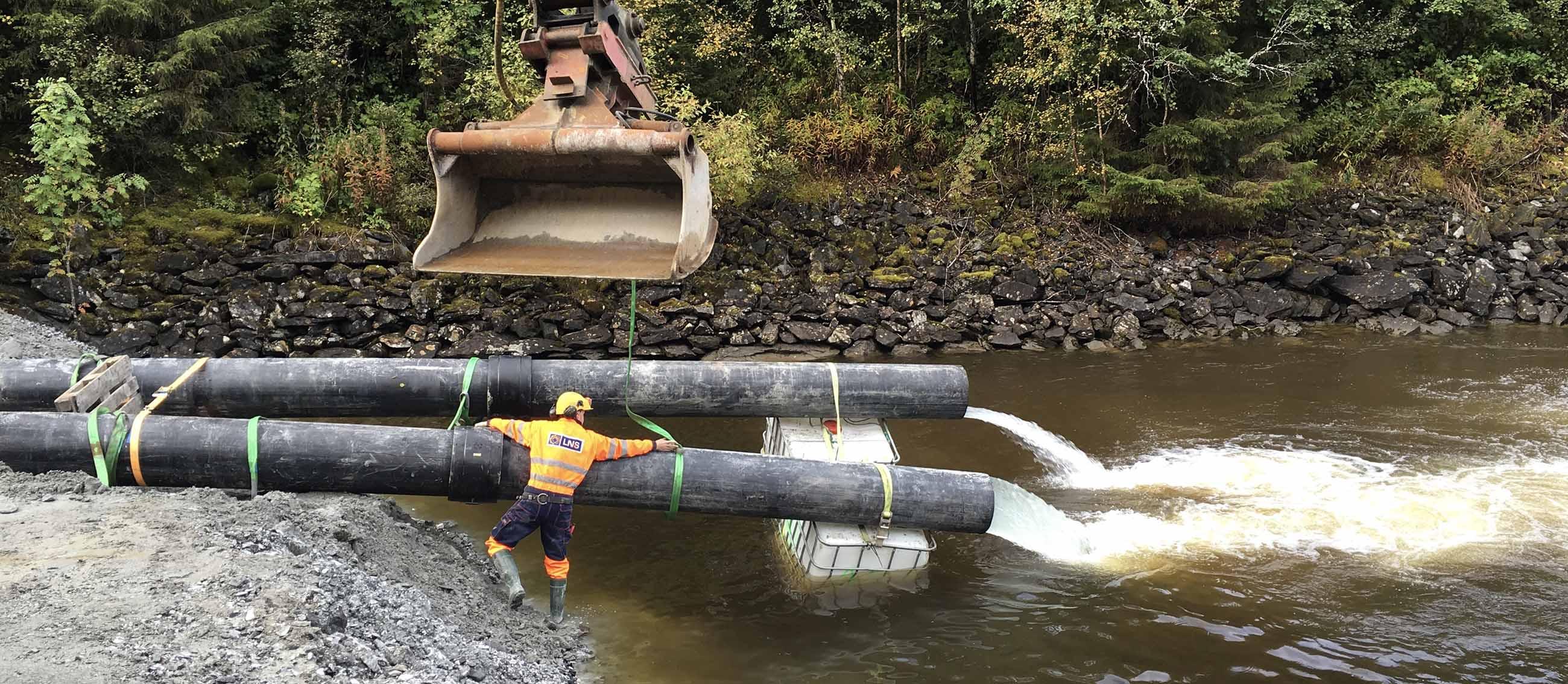 Stor lensepumpe som skyller ut vann i en elv